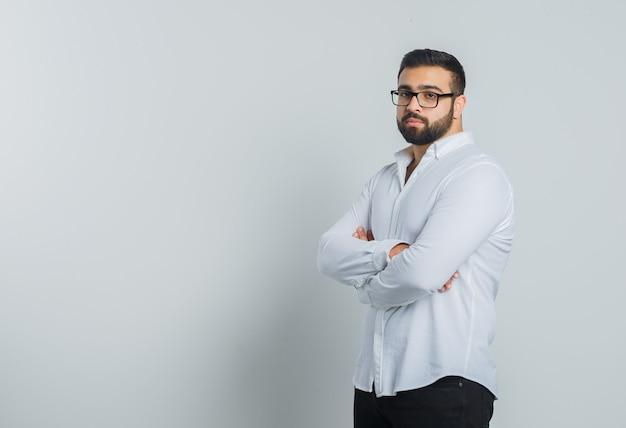 Jeune homme debout avec les bras croisés en chemise blanche, pantalon et à l'élégant