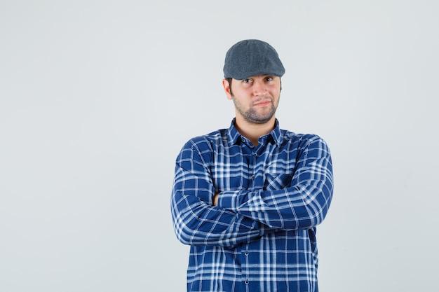 Jeune homme debout avec les bras croisés en chemise bleue, casquette et à la vue de face, confiant.