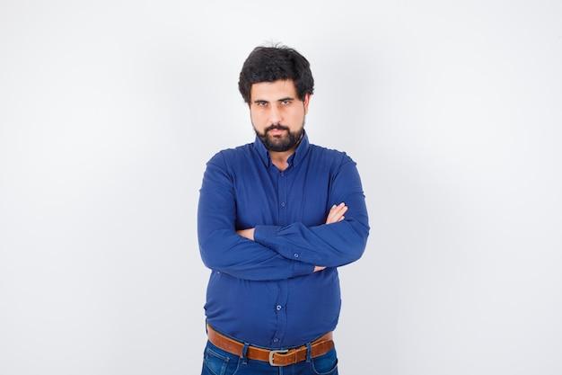 Jeune homme debout les bras croisés en chemise bleue et jeans et l'air sérieux. vue de face.