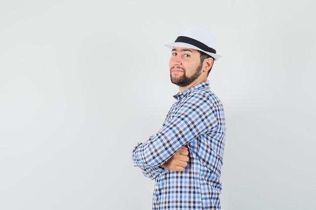 Jeune homme debout avec les bras croisés en chemise à carreaux, chapeau et à la confiance. .