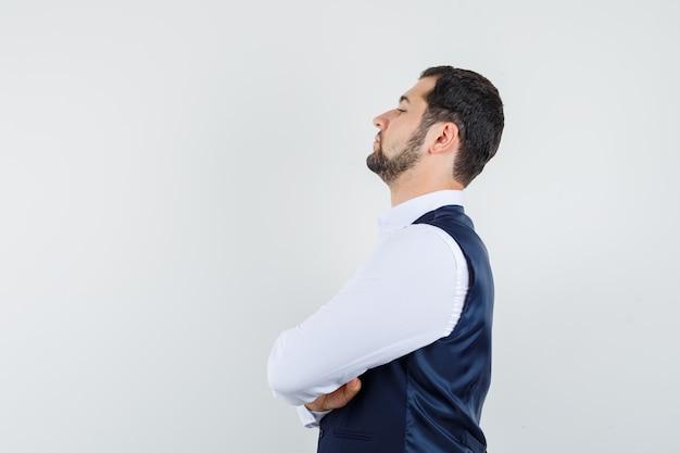 Jeune homme debout avec les bras croisés en chemise et gilet et à la confiance. .