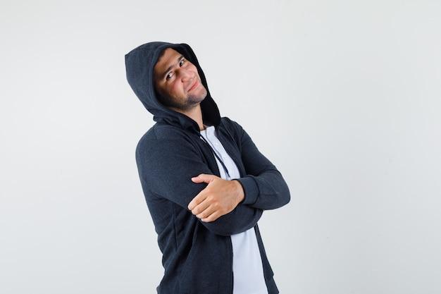 Jeune homme debout avec les bras croisés en t-shirt, veste et à la fierté, vue de face.