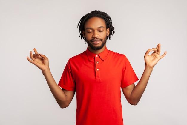 Jeune homme debout avec les bras levés et faisant du yoga exercice de méditation.