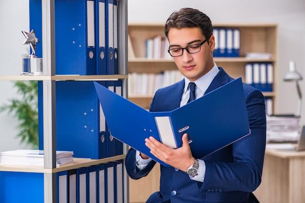Jeune homme debout à côté de l'étagère avec des dossiers