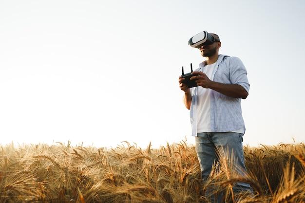 Jeune homme debout dans un champ de blé au coucher du soleil dans des lunettes de réalité virtuelle