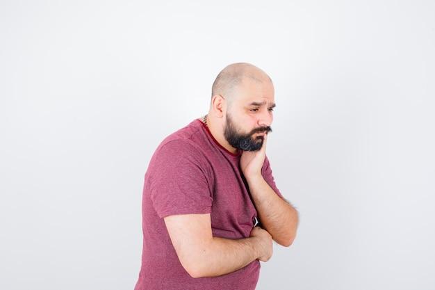 Jeune homme debout dans une pose de réflexion, la joue appuyée sur la paume en t-shirt rose et l'air pensif. vue de face.