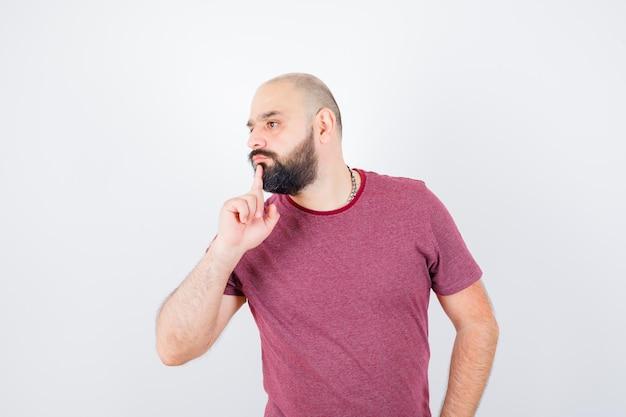 Jeune homme debout dans une pose de réflexion, regardant loin en t-shirt rose et l'air pensif. vue de face.