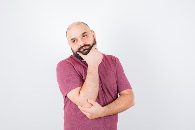 Jeune homme debout dans une pose de réflexion tout en mettant la main sur le menton en t-shirt rose et l'air pensif. vue de face.
