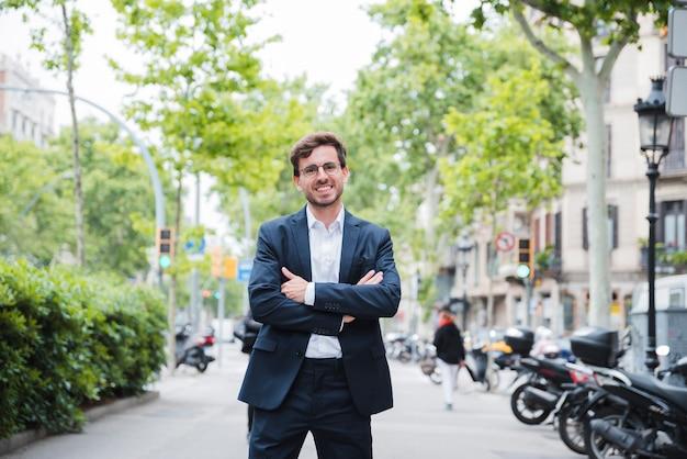 Jeune homme debout dans la rue avec son bras croisé en regardant la caméra