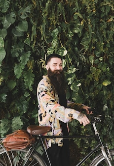 Jeune homme, debout, devant, vert, mur, feuilles, sien, bicyclette