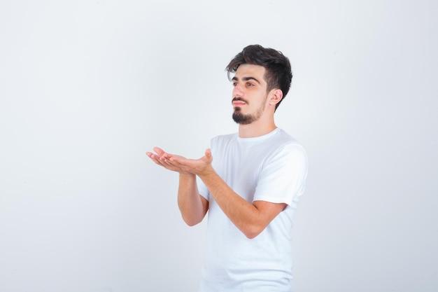 Jeune homme debout avec les mains en coupe en t-shirt blanc et à l'air confiant