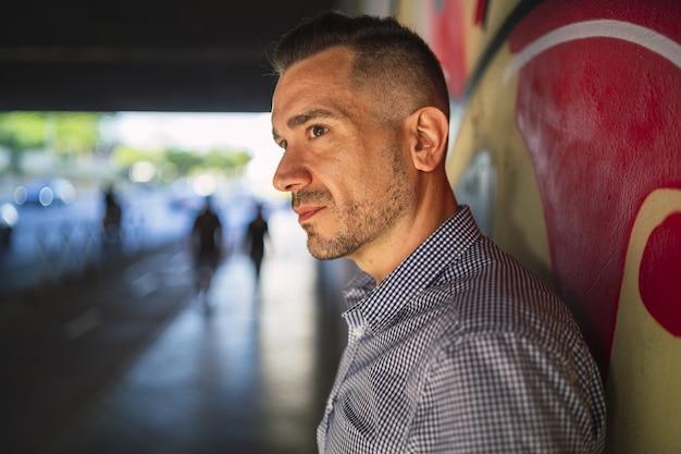 Jeune homme debout sur un mur peint avec une expression faciale sérieuse