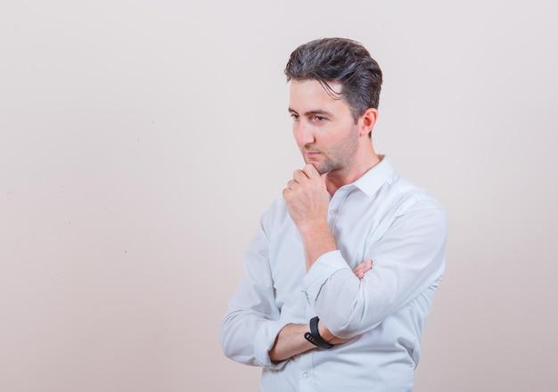 Jeune homme debout en pensant pose en chemise blanche et à l'intelligent