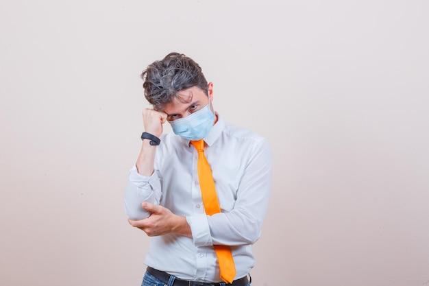 Jeune homme debout en pensant pose en chemise, cravate, jeans, masque et à l'air prudent