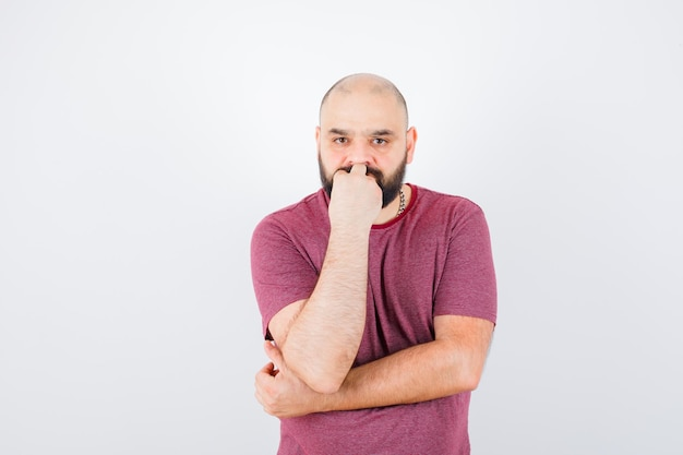 Jeune homme debout en pensant pose en t-shirt rose et l'air pensif. vue de face.