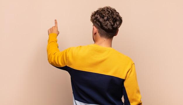 Jeune homme debout et pointant isolé