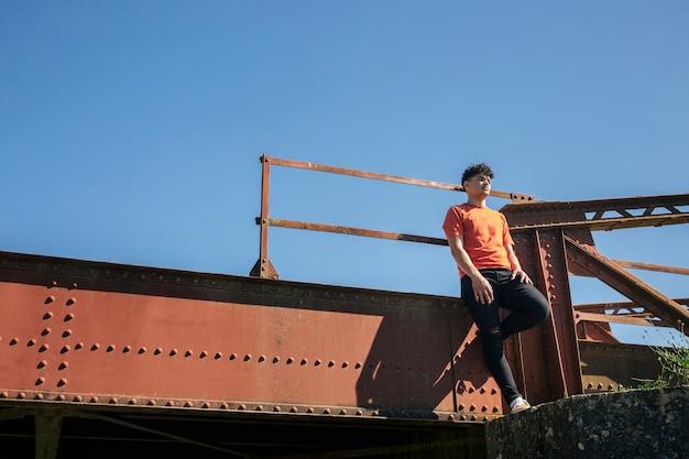 Jeune homme, debout, sur, pont métallique