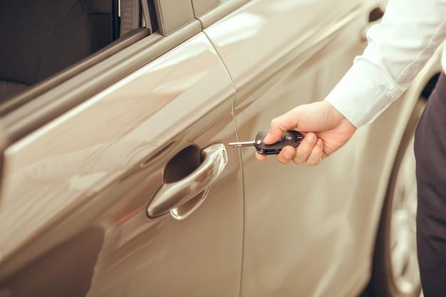 Jeune homme debout près du service de location de porte d'ouverture de voiture