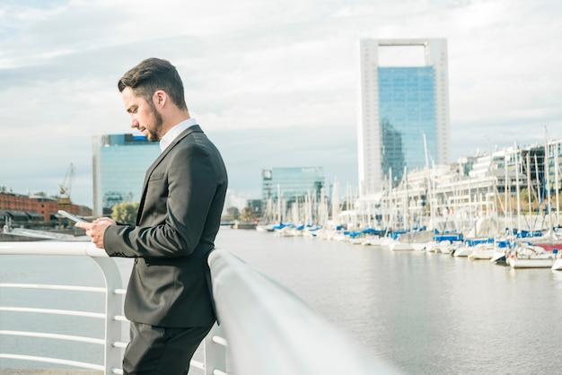 Jeune homme debout près de la rambarde à l'aide de téléphone portable