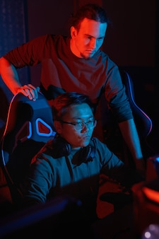 Jeune homme debout près de son ami et regarder comment il joue au jeu d'ordinateur sur ordinateur en club informatique