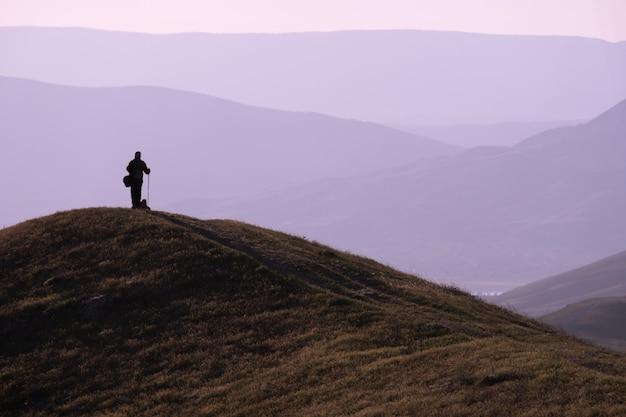Jeune homme debout avec sac à dos. randonneur sur la pierre au bord de la mer au ciel coucher de soleil coloré. beau paysage avec homme sportif berce la mer et les nuages au coucher du soleil. style de vie sportif