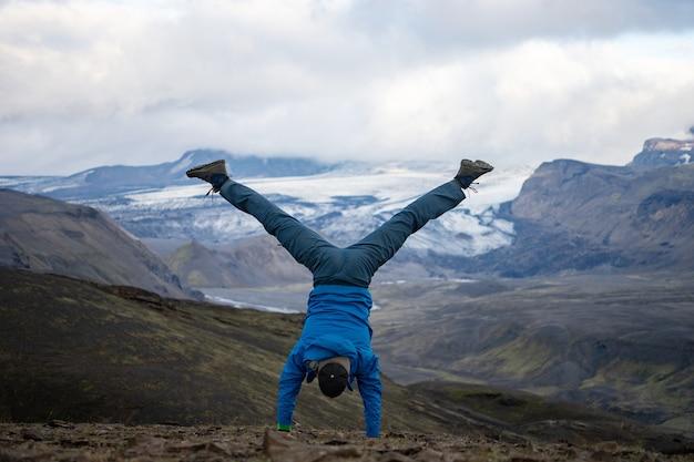 Jeune homme debout sur ses mains avec fond de montagne enneigée et glacier sur le chemin du sentier laugavegur