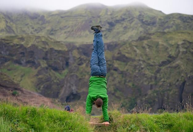 Jeune homme debout sur ses mains avec montagne brumeuse sur le chemin du sentier laugavegur, islande. promouvoir l'activité et un mode de vie sain.