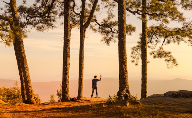 Jeune homme debout seul dans la forêt en plein air avec la nature du coucher du soleil sur le fond