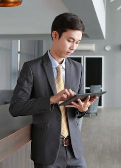 Jeune homme debout à la table sur le lieu de travail au bureau à l'aide de la tablette