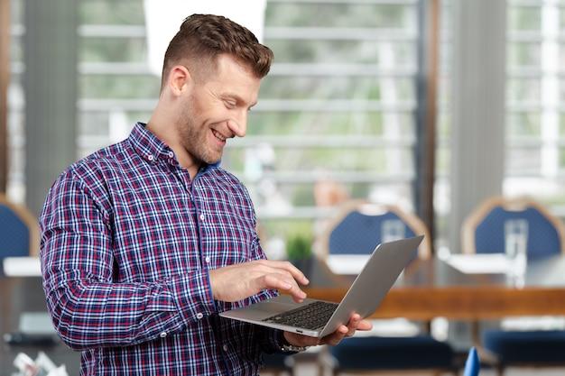 Jeune homme debout, tenant un ordinateur portable, travaillant.