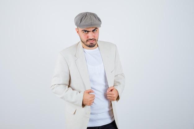 Jeune homme debout tout droit et posant à l'avant en t-shirt blanc, veste et casquette grise et l'air sérieux