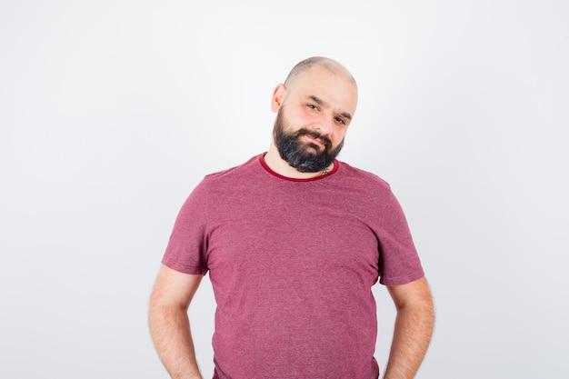 Jeune homme debout tout droit et se présentant à la caméra en t-shirt rose et l'air optimiste, vue de face.