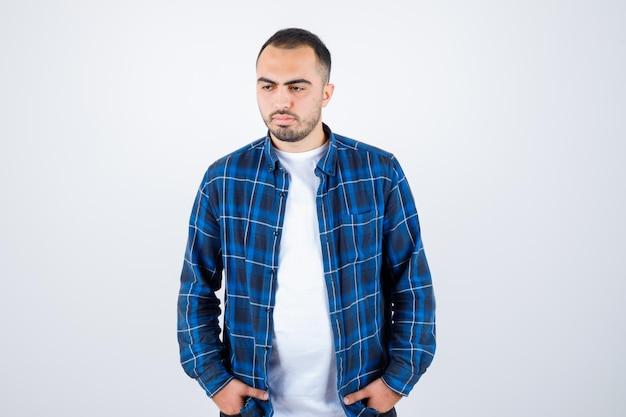 Jeune homme debout tout droit et tenant la main dans la poche en chemise à carreaux et t-shirt blanc et l'air sérieux