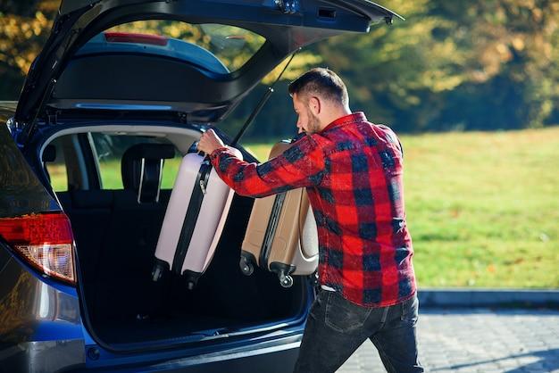Un jeune homme décharge ses bagages du suv après son retour de vacances d'été en famille.