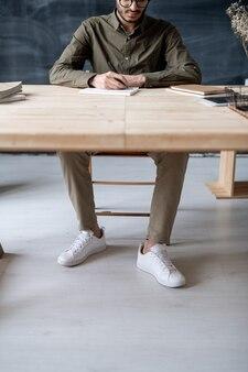 Jeune homme décontracté assis par une table en bois au bureau ou en classe et prendre des notes dans un cahier