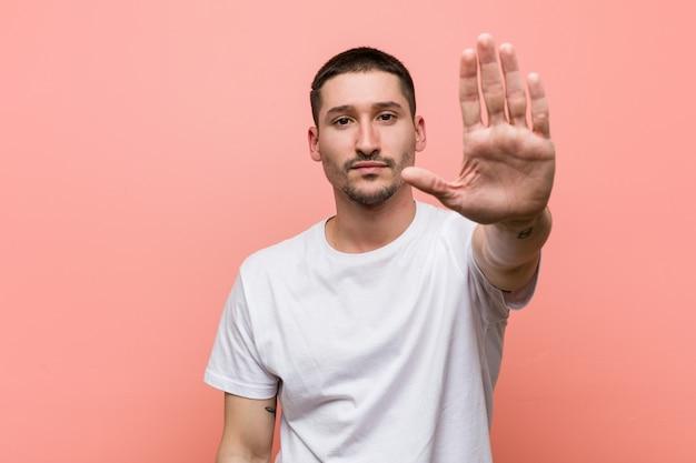 Jeune homme décontracté debout avec la main tendue montrant le panneau d'arrêt, vous empêchant