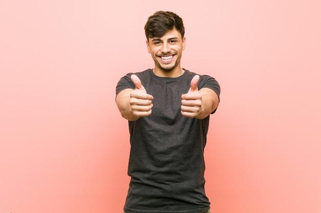 Jeune homme décontracté hispanique avec les pouces vers le haut, acclamations à propos de quelque chose