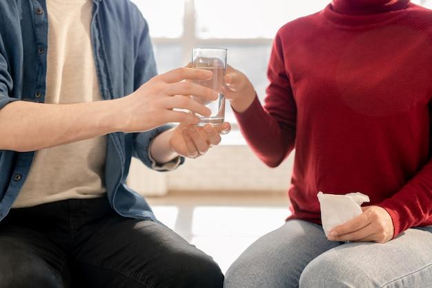 Jeune homme décontracté passant un verre d'eau pour contrarier un camarade de groupe avec un mouchoir pendant la session