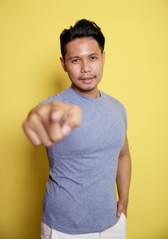 Jeune homme décontracté pointant la caméra très heureux isolé sur un fond de couleur jaune