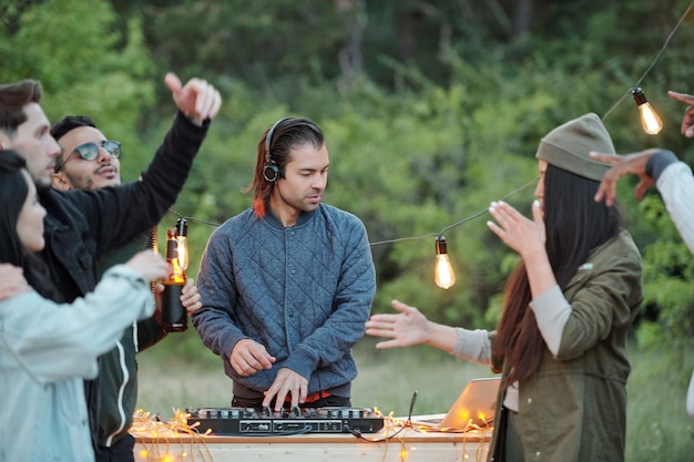 Jeune homme décontracté en veste et casque faisant de la musique pour ses joyeux amis interculturels dansant et profitant du week-end d'été