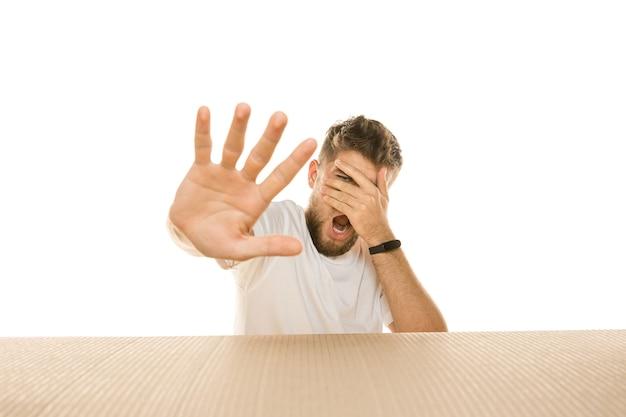 Jeune homme déçu ouvrant le plus gros colis postal isolé sur blanc. modèle masculin choqué sur le dessus de la boîte en carton regardant à l'intérieur.