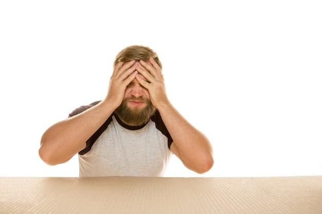 Jeune homme déçu ouvrant le plus gros colis postal isolé sur blanc