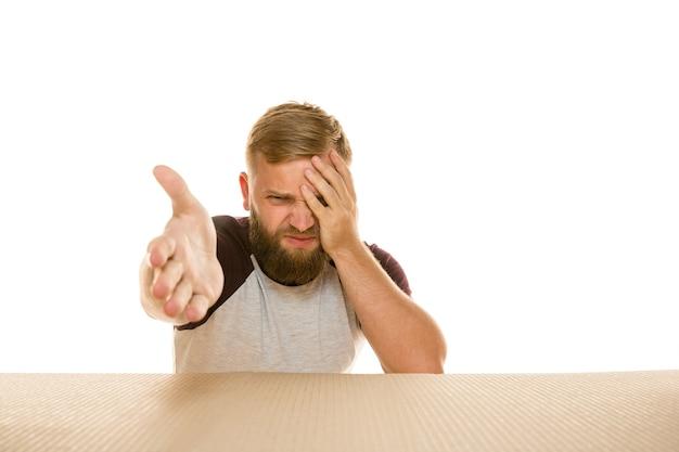 Jeune homme déçu ouvrant le plus gros colis postal