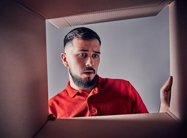 Un jeune homme déçu regarde un cadeau à l'intérieur d'une boîte en carton.