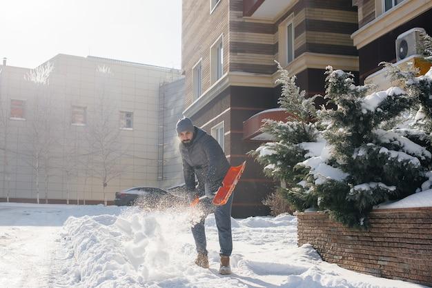 Un jeune homme dégage la neige devant la maison par une journée ensoleillée et glaciale. nettoyer la rue de la neige.