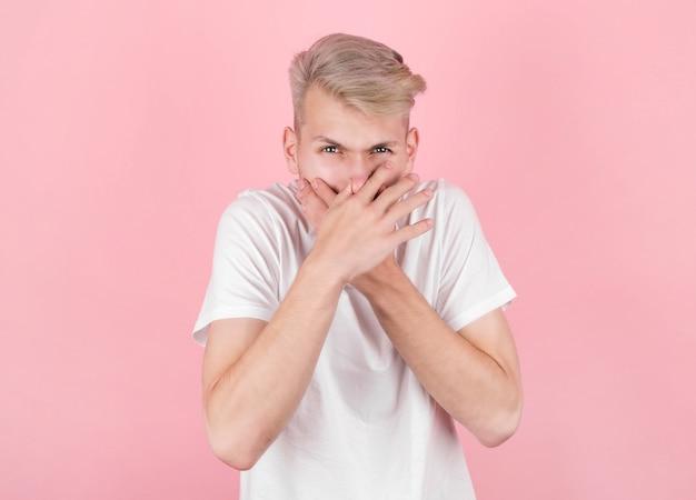 Jeune homme avec dégoût sur son visage rose. expression faciale des émotions négatives.