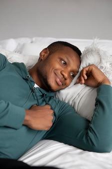 Jeune homme, délassant, dans lit