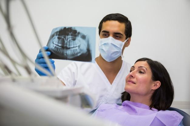 Jeune homme dentiste examinant les rayons x avec la patiente
