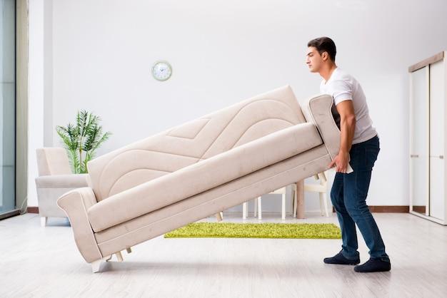 Jeune homme déplace des meubles à la maison