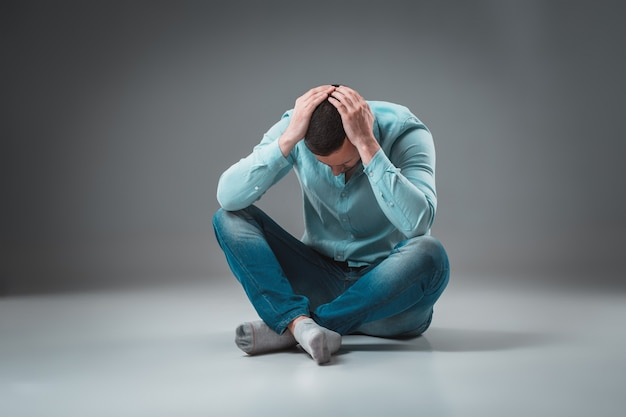 Jeune homme déprimé assis tenant sa tête avec les deux mains